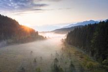 Sun Rays At Sunrise On Fog Covering The Wetland Of Pian Di Gembro Reserve, Aerial View, Aprica, Valtellina, Lombardy
