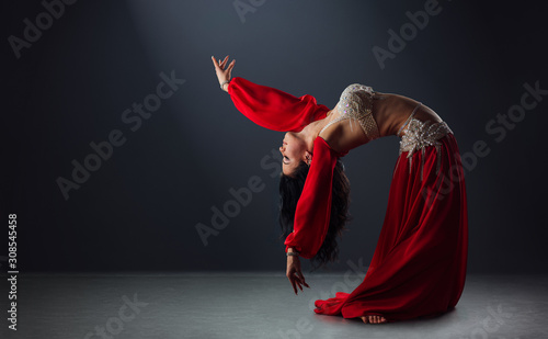 Fotografía  beautiful black-haired girl in red ethnic dress dancing oriental dances leaning