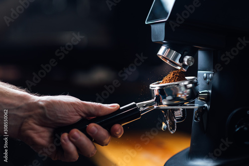 Fototapeta ground coffee pouring into a portafilter with a grinder obraz