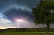 Baum in Landschaft mit Gewitter und Blitz