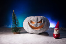 Christmas New Year Or Halloween Celebrate Background With Little Christmas Tree On Blurred Bokeh Snow Background With Horror Pumpkin