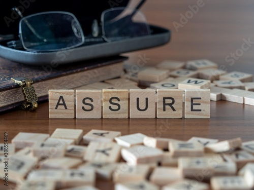 assure the word or concept represented by wooden letter tiles Canvas Print