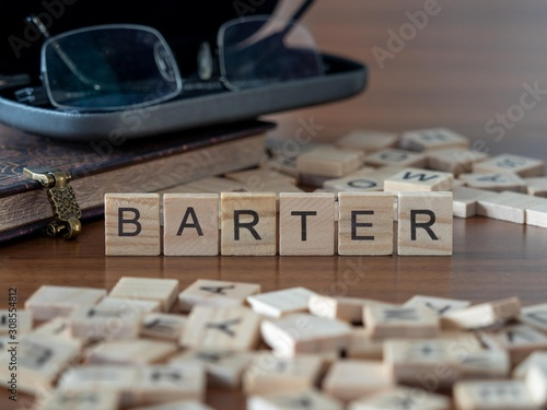 Photo barter the word or concept represented by wooden letter tiles