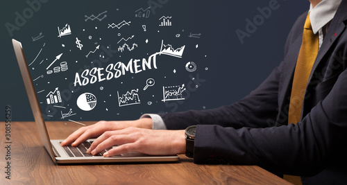 Businessman working on laptop with ASSESSMENT inscription, modern business conce Canvas Print