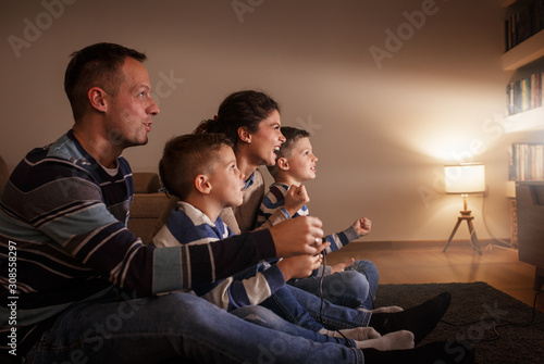 Obraz Parents with they children  sitting at home on pleasant evening and playing games on console.They challenge each other to win . - fototapety do salonu