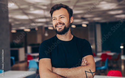 Obraz Cheerful guy with crossed arms in cafe - fototapety do salonu