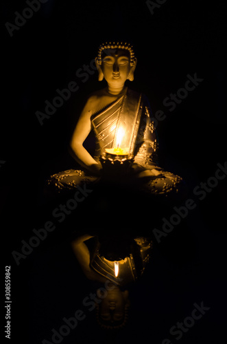 Foto Buddha sitting in meditation position with candles