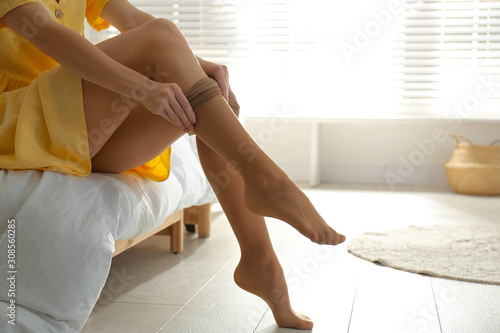 Fotografía  Young woman putting on tights in bedroom, closeup