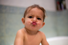 A Bathing Cute Baby Shows A Kiss And Looks At The Camera. Soft Focus, Close-up, Background - The Bathroom At Home In Blur