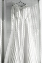 White Wedding Dress On The Clothes Hanger. Wedding Dress On The Balcony. Fashion Look