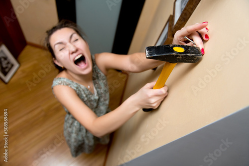 young woman screams, hitting a finger with a hammer Canvas Print