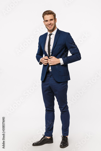 Obraz Vertical, full-length shot handsome, successful and wealthy young businessman in suit and tie, fasten buttons on jacket, smiling assertive, feeling confident and lucky, determined win case in court - fototapety do salonu