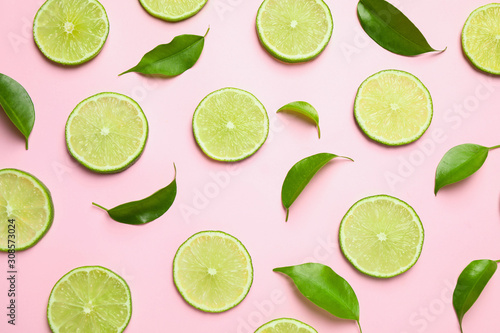 Fototapeta Juicy fresh lime slices and green leaves on pink background, flat lay