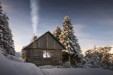 Fantastic Winter Landscape With Wooden House In Snowy Mountains. Smoke Comes From The Chimney Of Snow Covered Hut. Christmas Holiday Concept