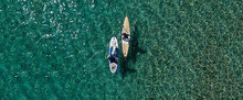 Aerial Drone Ultra Wide Panoramic Photo Of Unidentified Fit Man Paddling With His Cute Dog On A SUP Board Or Stand Up Paddle Board In Tropical Exotic Emerald Bay
