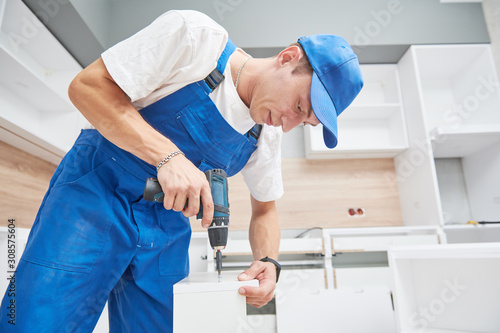 kitchen installation. Worker assembling furniture Canvas Print