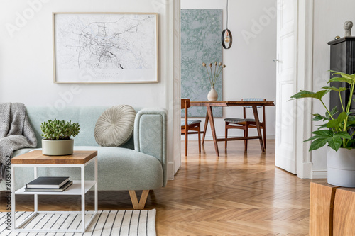 Stylish scandinavian living room with design mint sofa, furnitures, mock up poster map, plants and elegant personal accessories. Modern home decor. Open space with dining room. Template Ready to use.
