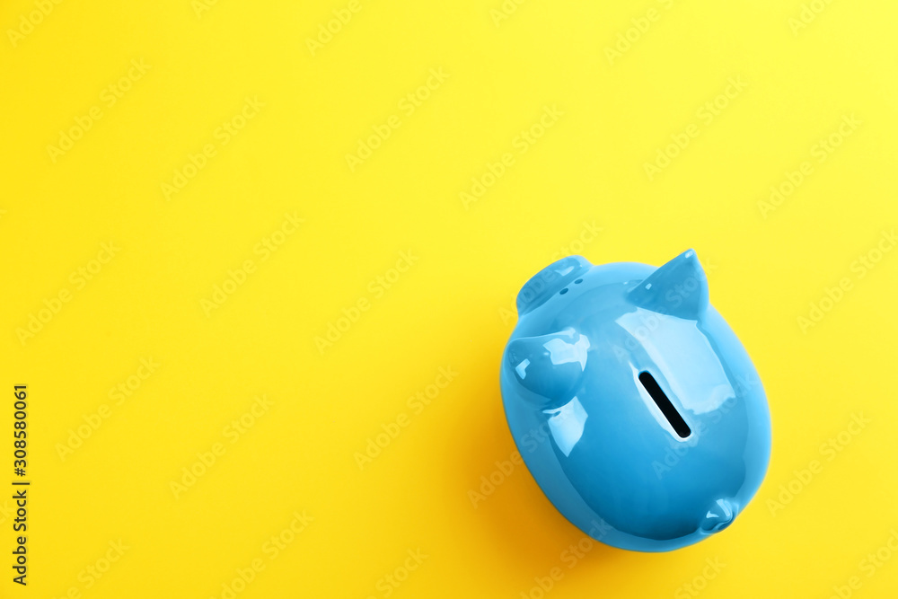 Fototapeta Blue piggy bank on yellow background, top view. Space for text