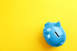 canvas print picture - Blue piggy bank on yellow background, top view. Space for text