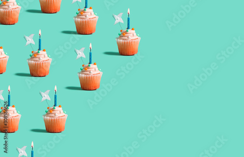 Tasty celebratory cupcakes with decorative lit candles Canvas Print