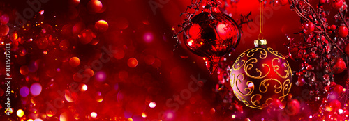 Christmas and New Year Red Decoration. Abstract Blurred Bokeh Holiday Background with beautiful baubles and Blinking Garland. Christmas Tree Lights Twinkling. Xmas backdrop art design - 308591283
