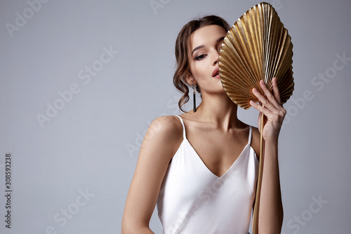 Fototapeta Portrait beautiful sexy pretty woman red lipstick jewelry earrings brunette hair cosmetic makeup fashion clothes beauty salon party date skin care perfect face silk blouse nail accessory tan
