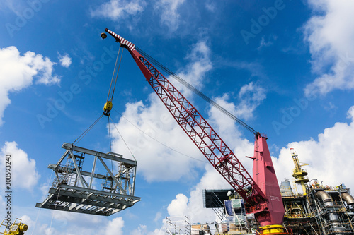фотография Offshore crane on board a construction work barge performing heavy lifting of a