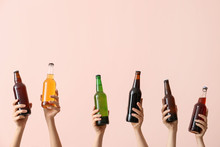 Hands With Bottles Of Beer On Color Background