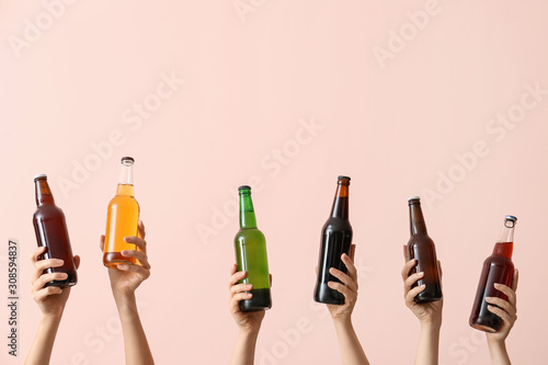 Photo Hands with bottles of beer on color background