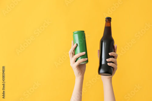 Hands with bottle and can of beer on color background Canvas Print