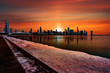 canvas print picture - Chicago's city skyline silhouette against a deep orange sunset reflecting off the frozen Lake Michigan in Illinois, USA.