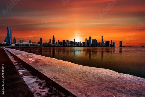 Foto auf Leinwand Kastanienbraun Chicago's city skyline silhouette against a deep orange sunset reflecting off the frozen Lake Michigan in Illinois, USA.