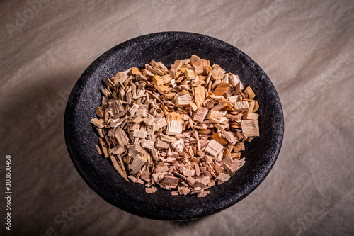 Valokuvatapetti Sawdust for smoking meat in a black bowl. On the paper