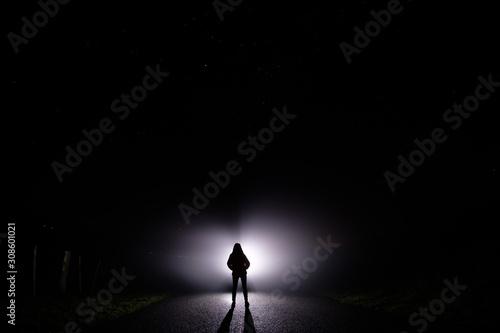 Fototapeta premium Sylwetka kobiety w ciemności. Fotografia nocna. Jasne światło świecące za ciemną tajemniczą postacią. Widmowa, mistyczna, surrealistyczna osoba stojąca.