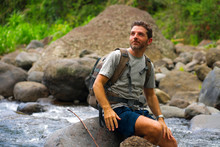 Young Happy And Attractive Man With Travel Backpack Hiking In River At Forest Feeling Free Enjoying Nature And Fresh Environment On Summer Trekking Journey
