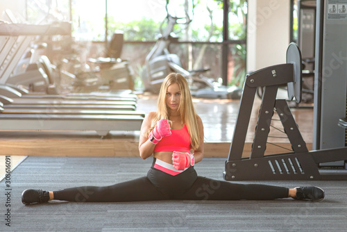 Photo Full-length portrait of sexy fit blonde in stylish sportswear and kickboxing gloves looking at camera and doing the splits while getting ready for training