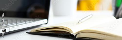 Silver pen lying on opened notebook sheet closeup