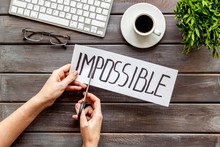 All Is Possible Concept. Hands Cut Word Impossible On Dark Wooden Office Desk