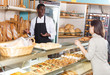 Baker selling baked products to female client