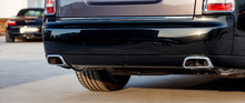Close-up Of A Black Luxury Car Bumper Of An Sedan With Two Side Turbo Exhaust Pipes Outdoors On Asphalt. Auto Service Industry. Air And Environment Pollution.
