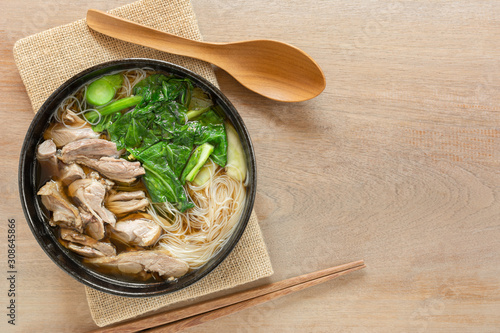 Cuadros en Lienzo top view of rice vermicelli soup with sliced duck meat in a ceramic bowl on wooden table