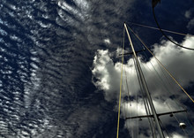 Nephology Art. A Beautiful Sky Cloudscape Scene, With White Altocumulus And Cumulus Cloud In A Mid Blue Sky With A Yacht Mast In Foreground.