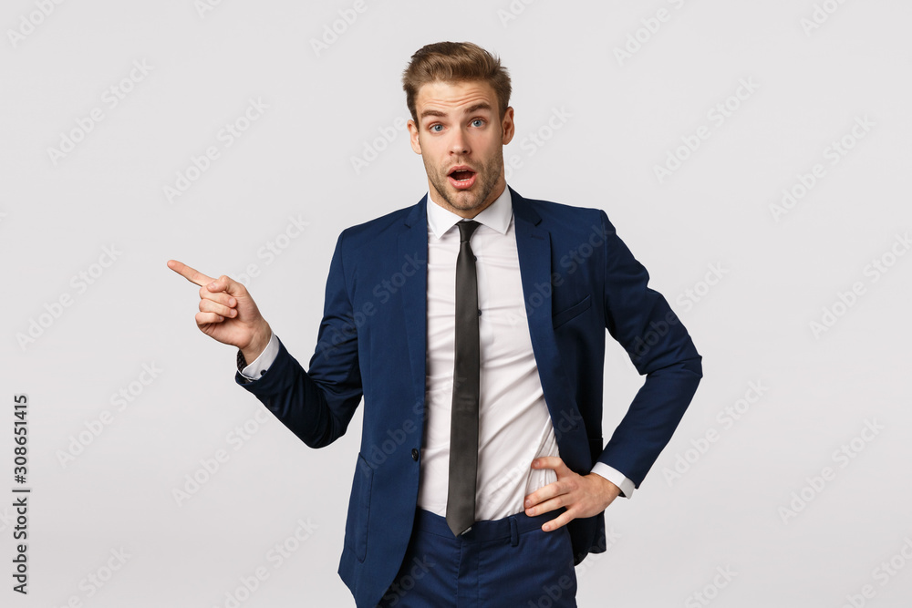Fototapeta Surprised, speechless young businessman with blond hair, bristle, wearing classic suit, starting career new company, asking question about coworker, pointing left and look amused, white background