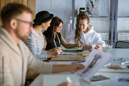 Fototapety, obrazy: Group of happy young women discussing creative ideas while working in studio