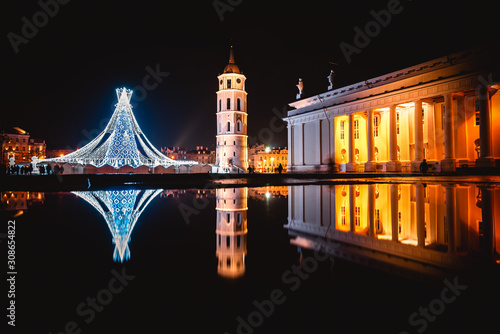 VILNIUS, LITHUANIA - DECEMBER 10, 2019: Christmas tree in a shape of chess queen in the city cathedral square and its reflection on water.
