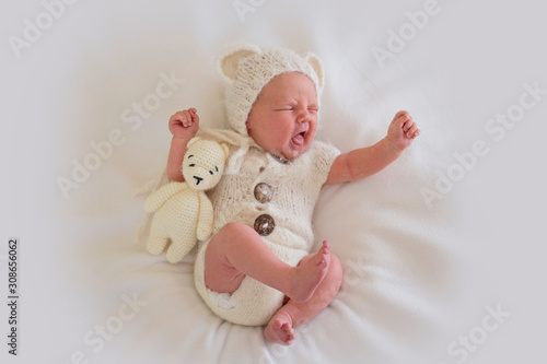 Photo  Newborn baby in a suit is emotionally grimacing