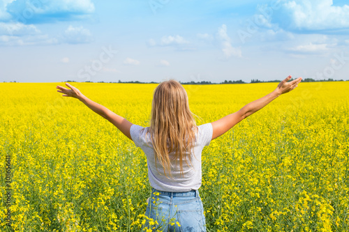 Obraz The girl spread her arms while standing with her back in the field. Wish fulfillment concept - fototapety do salonu