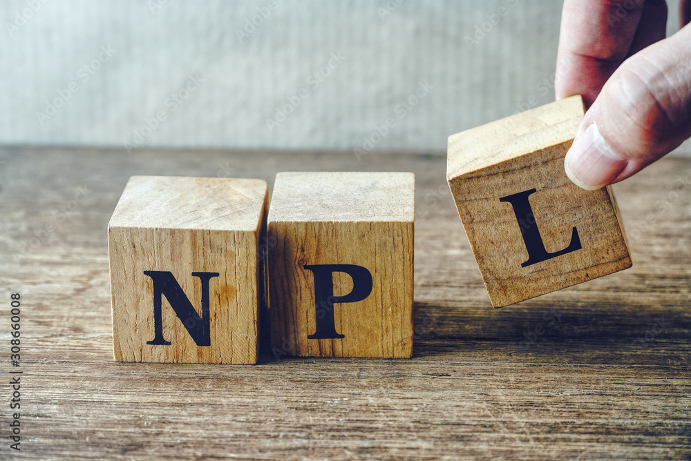 "Hand pick up wood cube block which have text""NPL"" , stock investment concept."