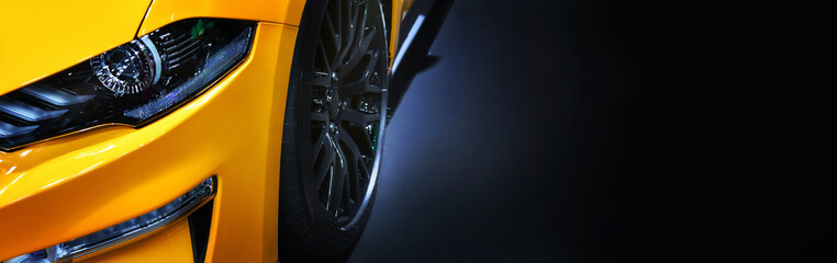 Front headlights of yellow modern car on black background,copy space