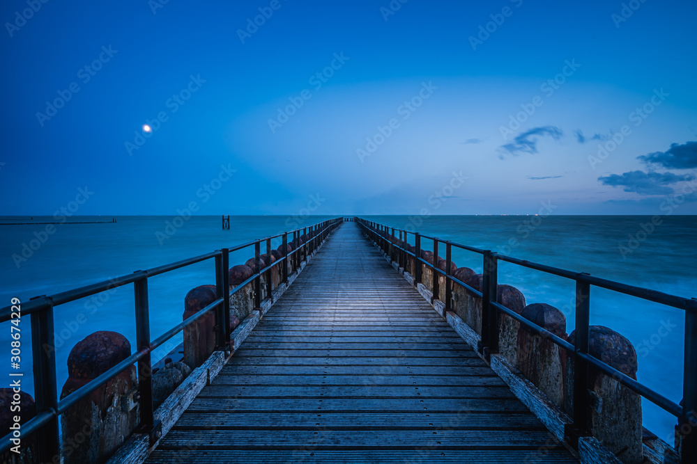 Fototapeta Long wooden pier extends over water toward the horizon. A leading line to the horizone